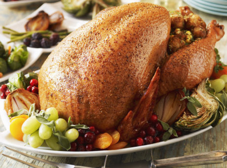 Whole Roast Turkey on a Platter with Fruit; Side Dishes on Table